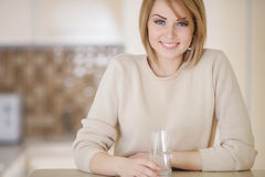 Beautiful woman in the kitchen with a glass of water Stock Photo