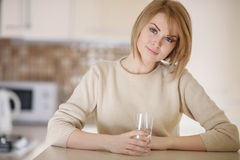 Beautiful woman in the kitchen with a glass of water Royalty Free Stock Photos