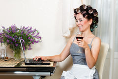 Beautiful woman in the kitchen with notebook. Housewife in the dining room with notebook and glass of wine Stock Image