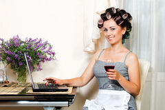 Beautiful woman in the kitchen with notebook. Housewife in the dining room with notebook and glass of wine Royalty Free Stock Image