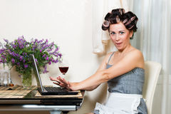 Beautiful woman in the kitchen with notebook. Housewife in the dining room with notebook and glass of wine Stock Photography