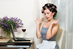 Beautiful woman in the kitchen with notebook. Housewife in the dining room with notebook and glass of wine Royalty Free Stock Photo