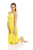 Beautiful woman kneelin in yellow dress. Royalty Free Stock Photography