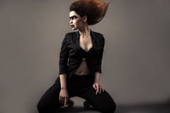 Beautiful woman kneeling with lush hair and dark makeup royalty free stock photography