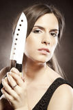 Beautiful woman with a knife Royalty Free Stock Image