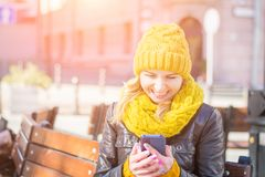 Beautiful woman in a knitted hat and scarf sits on a bench and laughs while looking at the screen of her smartphone. City street lifestyle stock photos