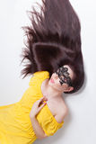 Beautiful woman in lace carnival mask. Beautiful brunette woman in carnival black lace mask with long shiny thick dark hair lays in yellow dress. Clear Young stock image