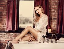 Beautiful woman in a lace robe sits near a jacuzzi in the spa Stock Images