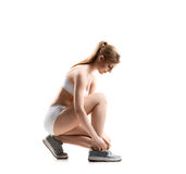 Beautiful woman in lacing her training shoes Royalty Free Stock Images