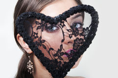 Beautiful woman with lacy heart. Beautiful young woman looking through the lacy heart royalty free stock photography