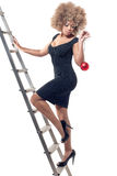 Beautiful woman on ladder holding a Christmas ball Stock Photo