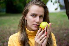 Girl with apple. Beautiful woman lady girl holding big yellow apple, natural beauty face, relax in the garden autumn park. day picnic in the village, fresh air Royalty Free Stock Photos