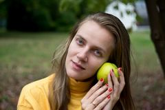 Girl with apple. Beautiful woman lady girl holding big yellow apple, natural beauty face, relax in the garden autumn park. day picnic in the village, fresh air Royalty Free Stock Photo
