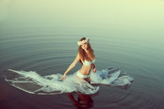 Beautiful woman in a lake at night. Girl at sunset in the lake. Royalty Free Stock Photo