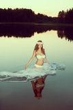 Beautiful woman in a lake at night. Girl at sunset in the lake. Royalty Free Stock Photography
