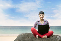 Beautiful woman with laptop at the beach Royalty Free Stock Photos