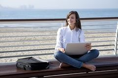 Beautiful woman with laptop and headset by the sea Royalty Free Stock Photo