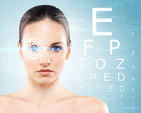 Beautiful woman with laser hologram and test vision table over c Royalty Free Stock Images