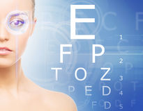 Beautiful woman with laser hologram and test vision table over c Royalty Free Stock Image