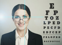 Beautiful woman with laser hologram and test vision table over d Royalty Free Stock Photography
