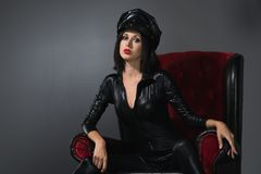 Woman in latex suit on a dark background. Beautiful woman in latex suit in chair on a dark background royalty free stock photo