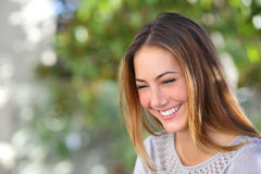 Beautiful woman laughing happy outdoor. With a green unfocused background Stock Image