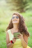 Beautiful woman laughing in the park. Reading e-book Royalty Free Stock Photos