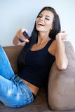 Beautiful woman laughing at the television Stock Image