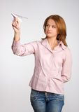 Beautiful woman launching paper plane up Stock Photo