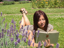 Beautiful woman in the lavender fields. Young red woman reading a book lying on the grass Royalty Free Stock Photo