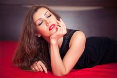 Beautiful woman laying on bed with closed eyes Stock Photography