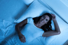 Beautiful woman laying in the bed at night. A young, beautiful woman relaxing in the bed at home at night Stock Images