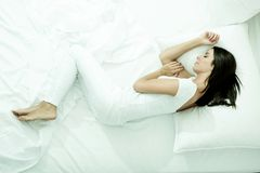 Beautiful woman laying in the bed. A young, beautiful woman relaxing in the bed at home Stock Photos