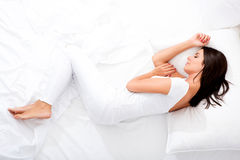 Beautiful woman laying in the bed. A young, beautiful woman relaxing in the bed at home Stock Photo