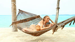 Beautiful woman laying and drinking from coconut stock video footage