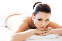 Beautiful woman laying on a mat having a smell of aroma in spa salon Stock Photo