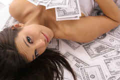 Beautiful woman laying in money. Shot of a beautiful woman laying in money Royalty Free Stock Image