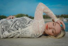 Beautiful woman laying near the river. Photo is taken near the beach Stock Image