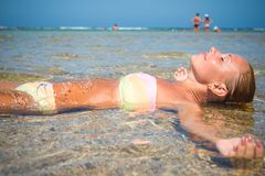 Beautiful woman laying in sea. On a hot summer day Stock Photos