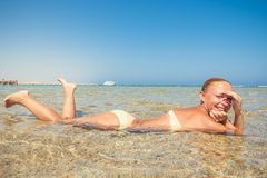 Beautiful woman laying in sea. On a hot summer day Royalty Free Stock Images