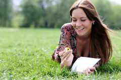 Beautiful woman lays on a grass in park with a diary in ha Royalty Free Stock Photography