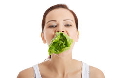 Beautiful woman with leaf of lettuce in mouth. Royalty Free Stock Photos