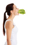 Beautiful woman with leaf of lettuce in mouth. Royalty Free Stock Photography