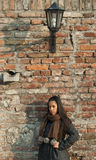 Beautiful woman leaned against brick wall Royalty Free Stock Image