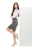 Beautiful woman leaning against big white poster. Beautiful young woman over white background Stock Photography