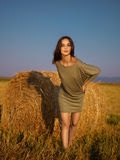 Beautiful woman leaning hay stack enjoying breeze Stock Photography