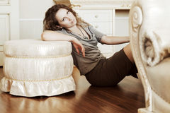 Beautiful woman leaning on the ottoman. Stock Photography