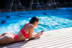 Beautiful woman leaning on poolside and typing a text message on cellphone Stock Photo