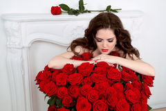 Beautiful woman leaning on the red roses bouquet in interior. Va Stock Photography