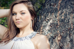 A beautiful woman leaning on tree in park Stock Photos